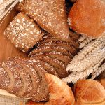 Variety of nutritional breads, ranging from simple white to whole wheat, freshly home baked on burlap, jute cloth